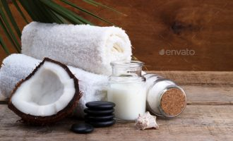 Spa setting and health care items, coconut,body oil,bath salt,milk,massage stones and towels, on wooden board
