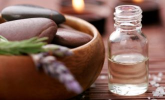 bottle of essential oil, massage stones,candles,lavander and bath-salt in a tight composition